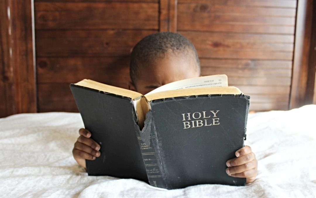 A young child reading a Bible in bed