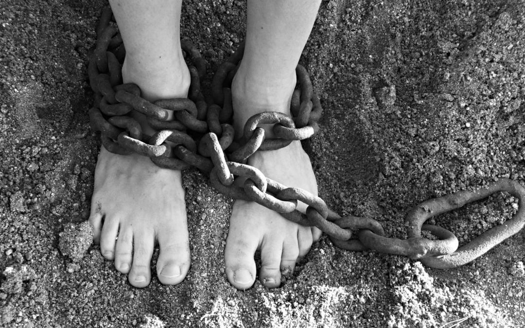 A person's feet on sand wrapped in chains