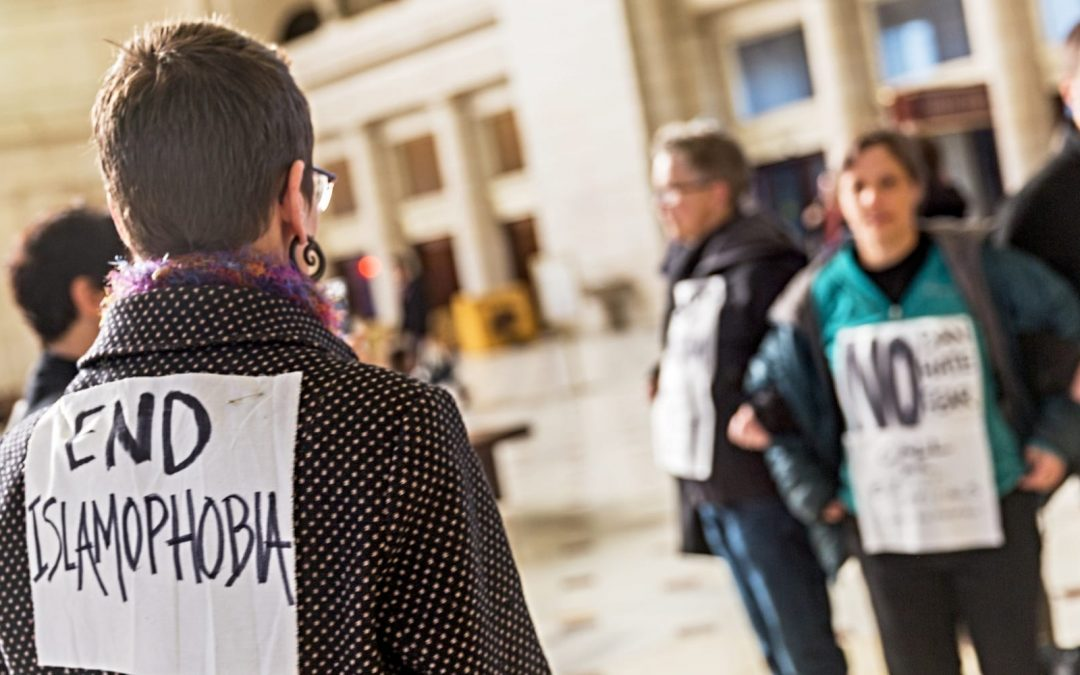 A woman wearing a sign that say end islamophobia