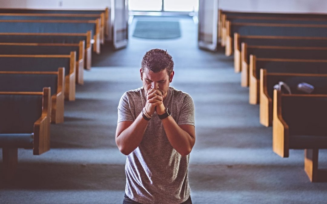 A man on his knees praying in an empty church