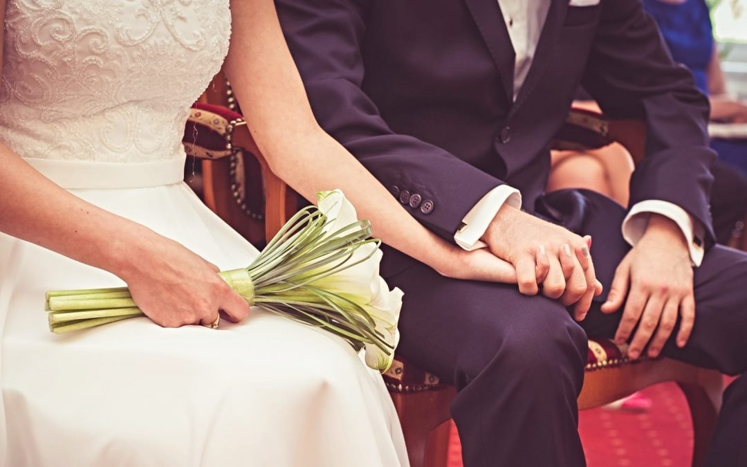 A bride and groom holding hands at their wedding
