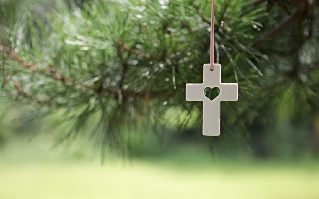 A white cross ornament handing on a Christmas tree