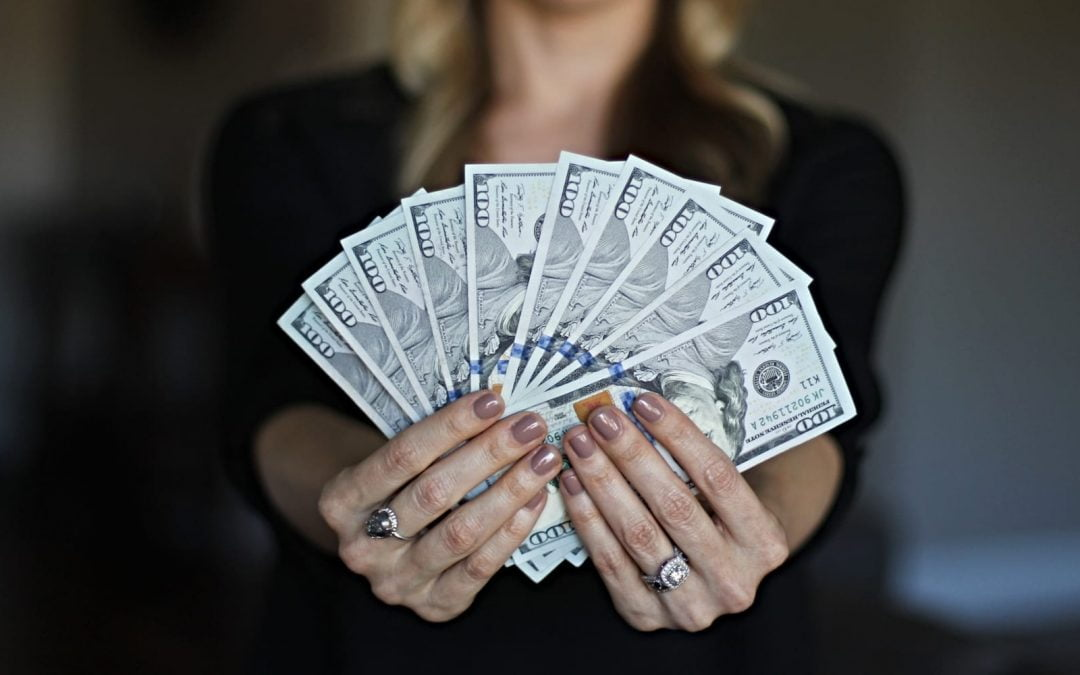 A woman holding $100 bills fanned out