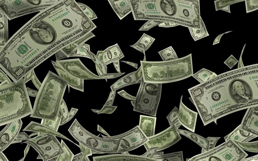 $100 bills falling down against a black backdrop