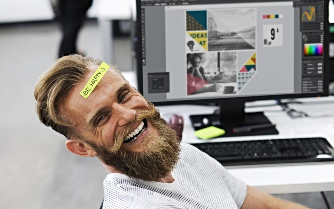 A man in an office smiling with a note on his forhead that says be happy