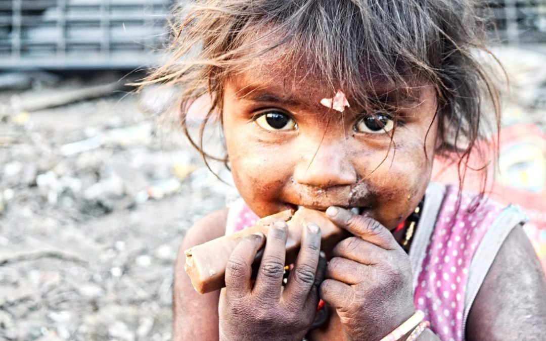 A young girl covered in dirt eating a snack in India