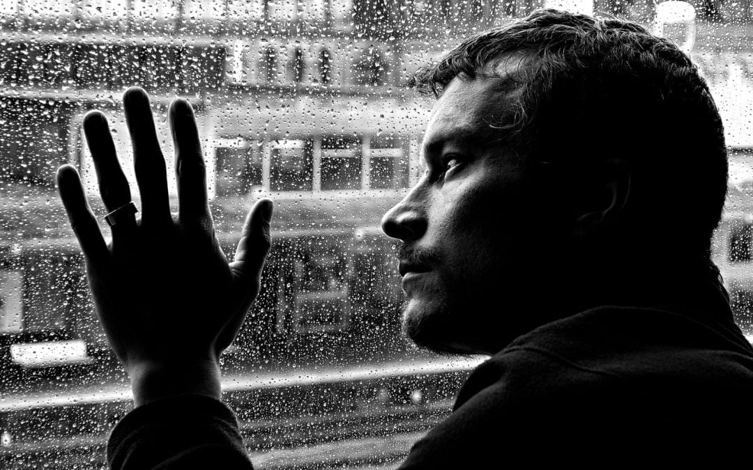 A man looking at a rain-covered window