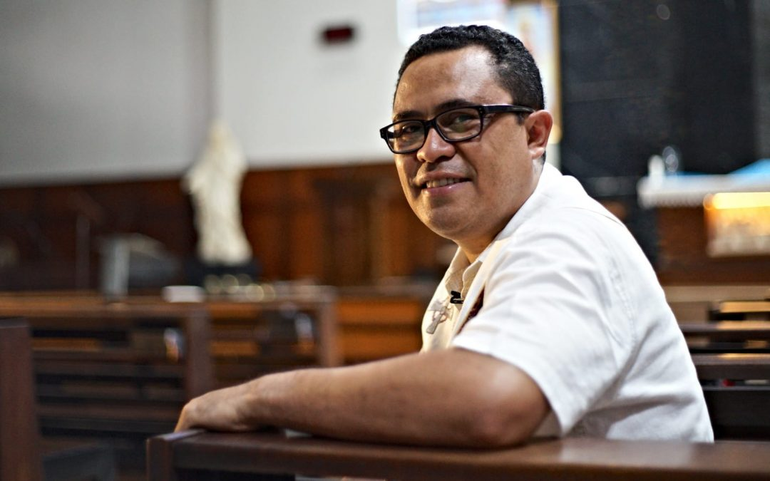 A pastor sitting in a church pew alone