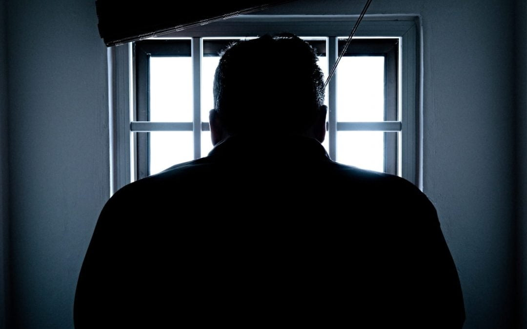 A man looking out the window of a prison cell