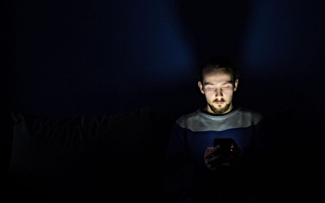 A young man in a dark room staring at his phone