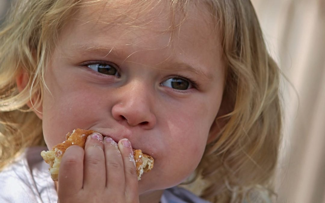 A young girl eating a piece of bread