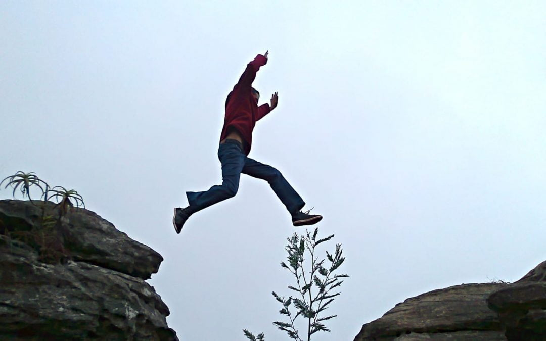 A man leaping across a chasm between rocks