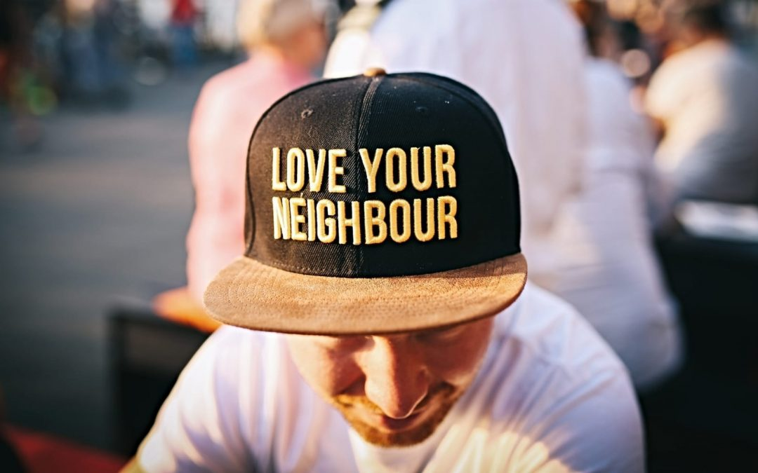 A man wearing a hat saying love your neighbor