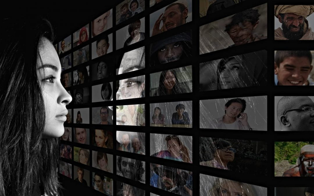 A woman looing at TV screens filled with people's faces