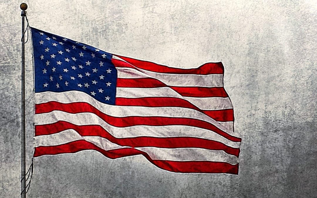 A U.S. flag in front of a grey background