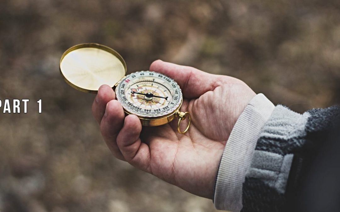 A person's hand holding a compass