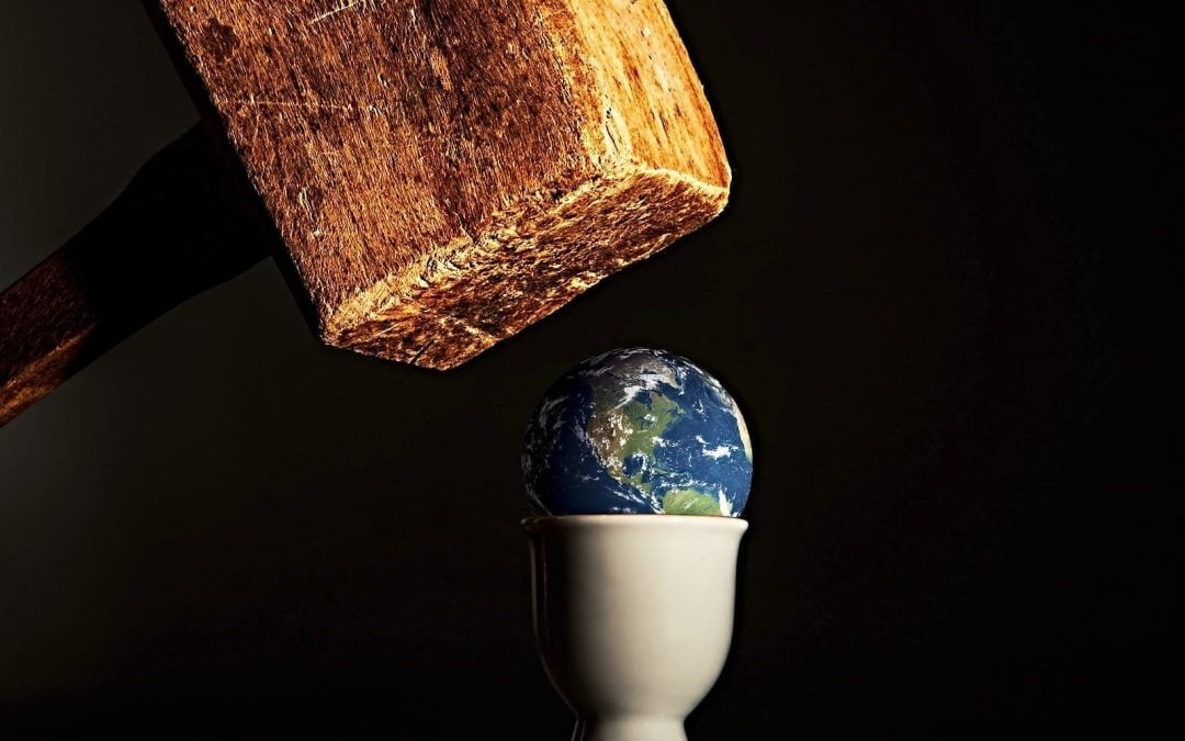 A large mallet coming down on top of a small globe