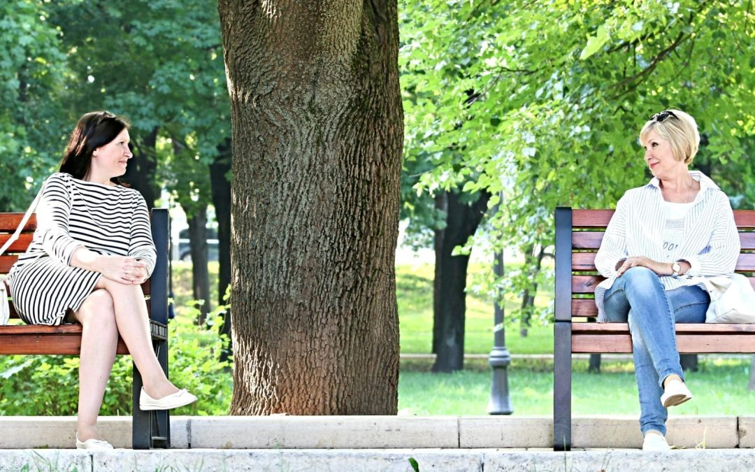 Two women sitting on benches in the park