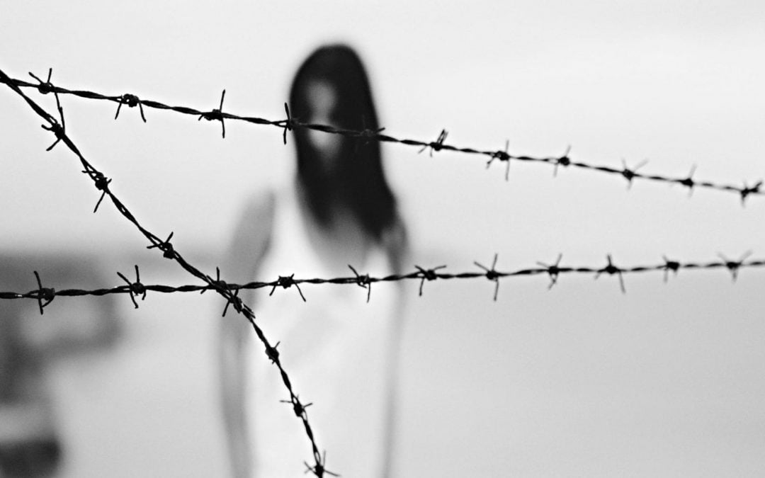 A woman blurred in the background with barbed wire in the foreground