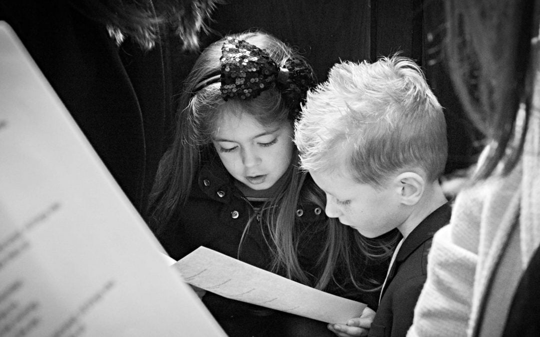Two young children looking at a piece of paper