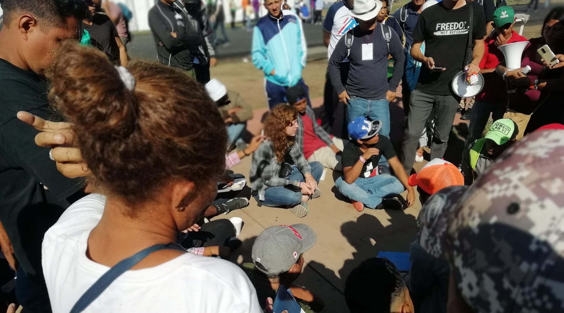 Immigrants sitting on the ground