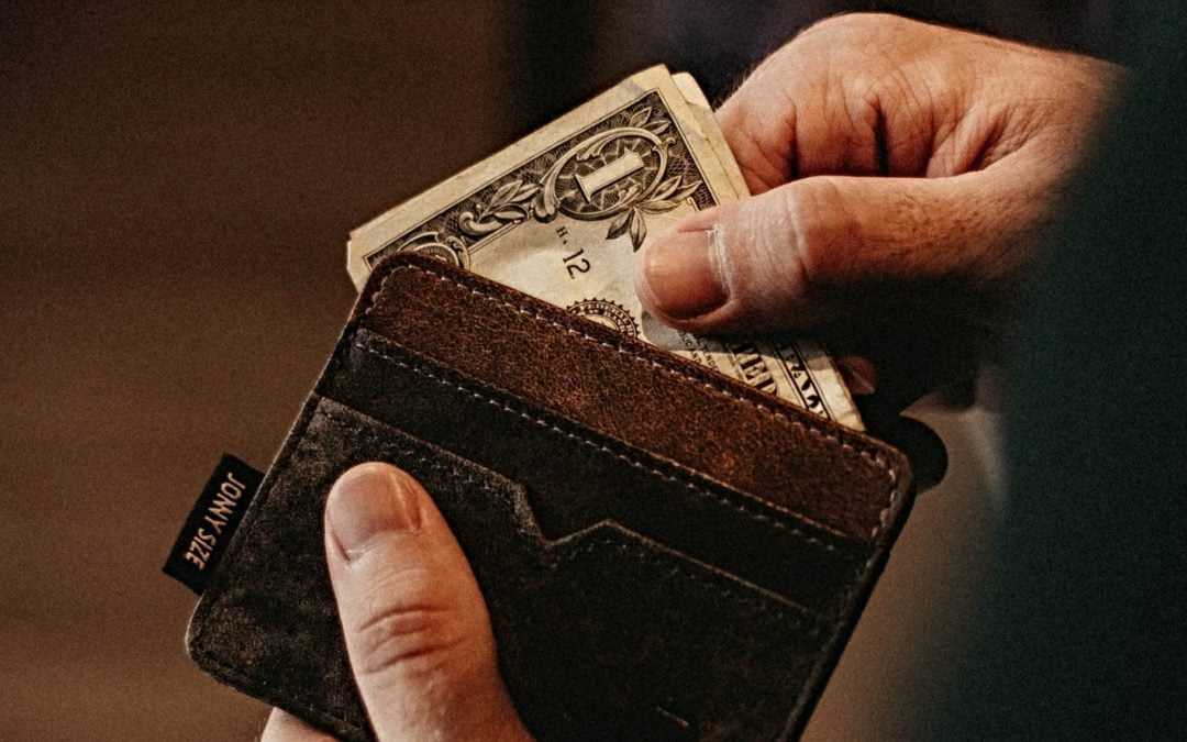 A man taking money out of a wallet
