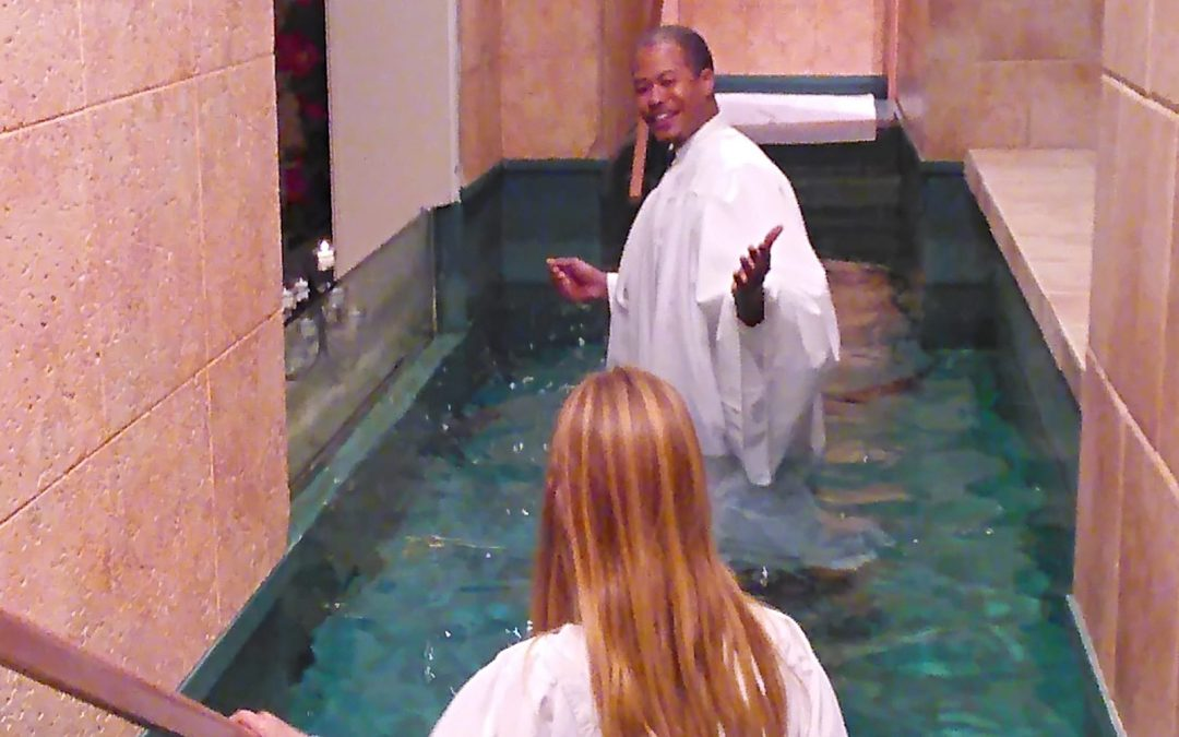 Timothy Peoples baptizing a young girl