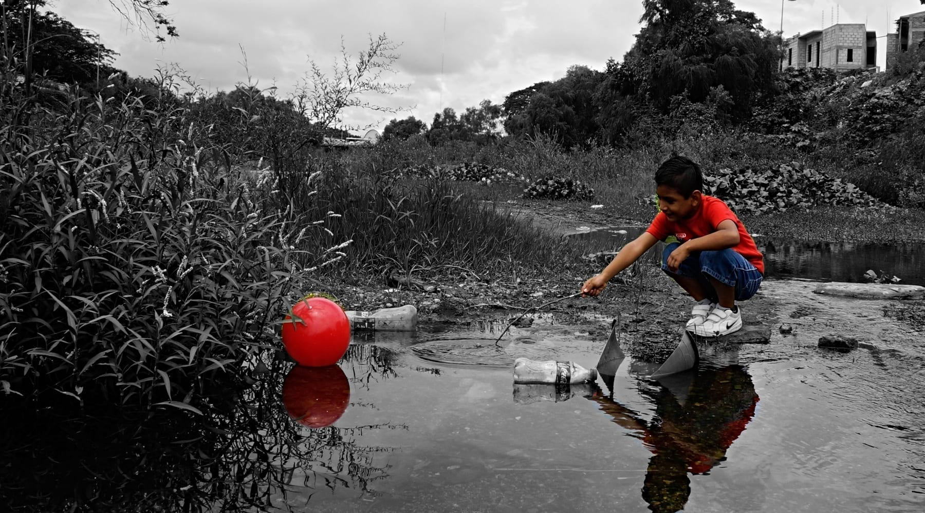 A young boy trying to get his red ball out of polluted water