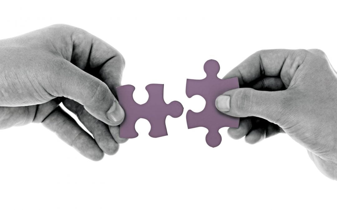 Hands holding puzzle pieces together