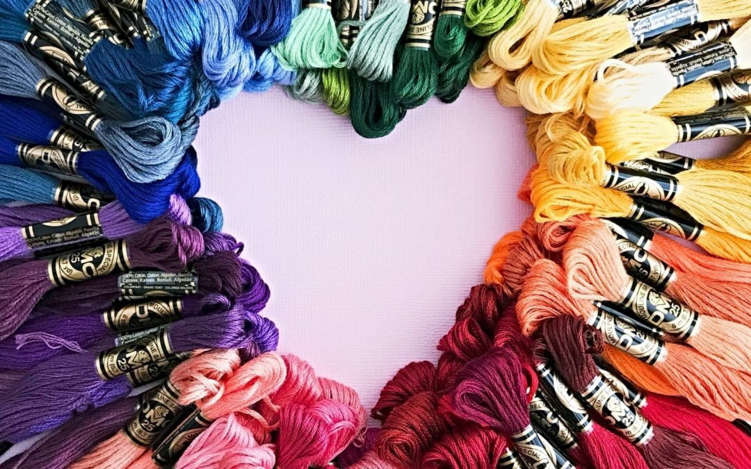 Colorful yarns arranged into the shape of a heart