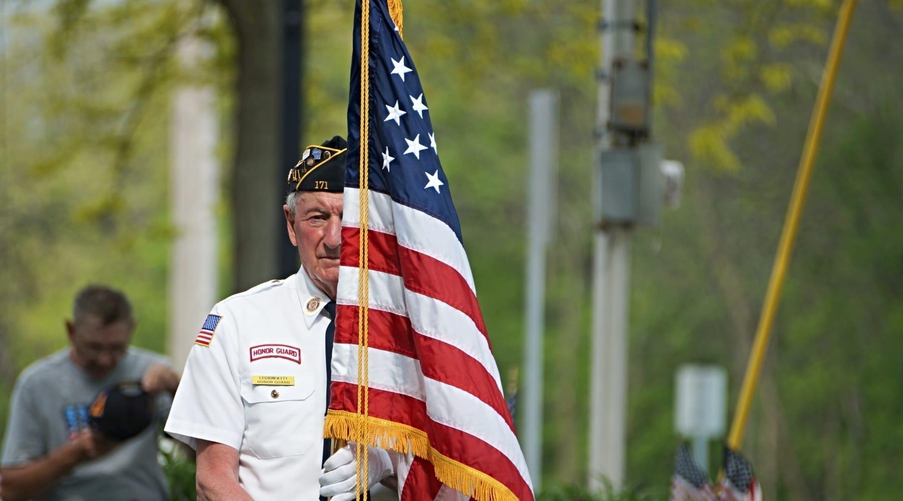 A military veteran carrying a U.S. flag