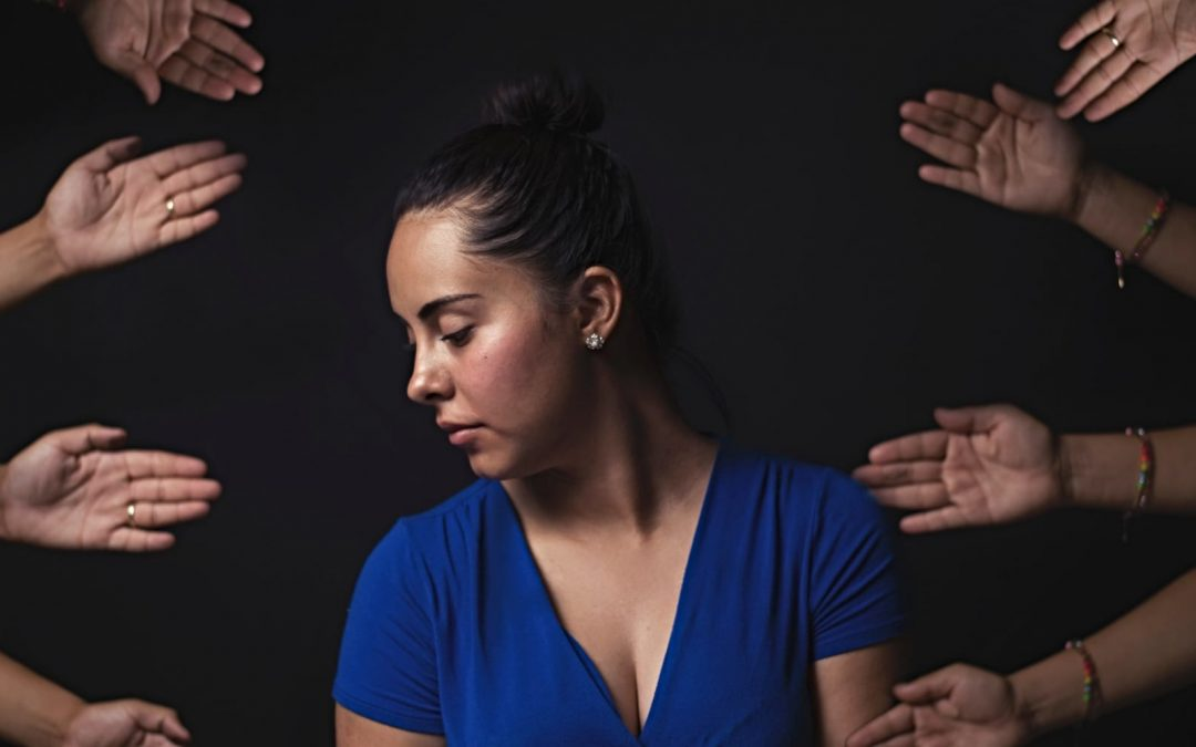 A woman sitting with hands reaching out to her