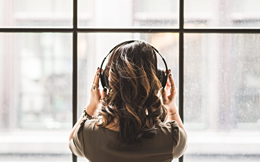 A woman looking out the window wearing headphones
