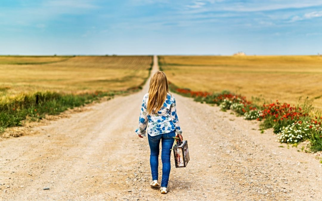 A woman carrying a suitcase walking down a dirt road