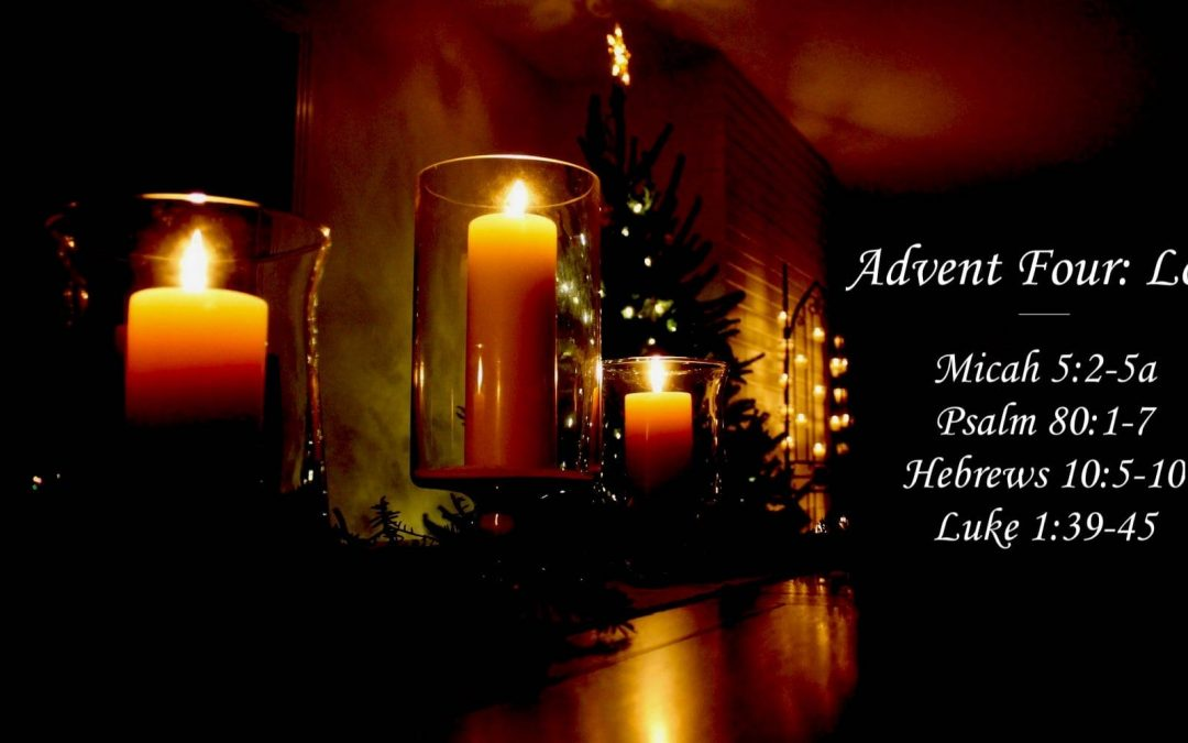 A dark room lit only by candle light and a Christmas tree