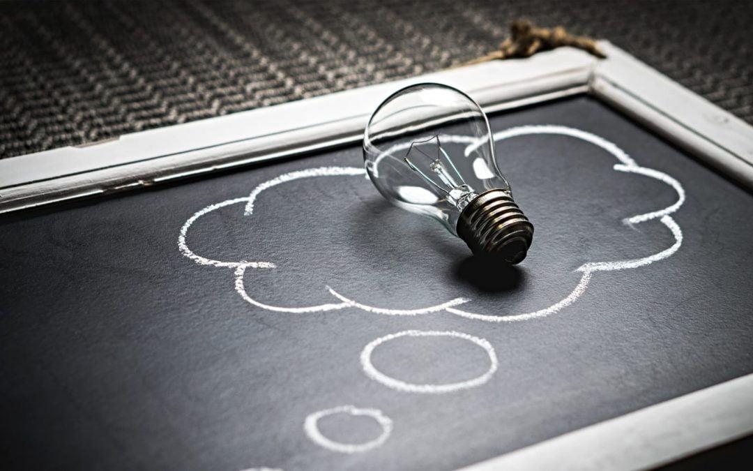 A light bulb sitting on a chalk board with an idea cloud drawn around it