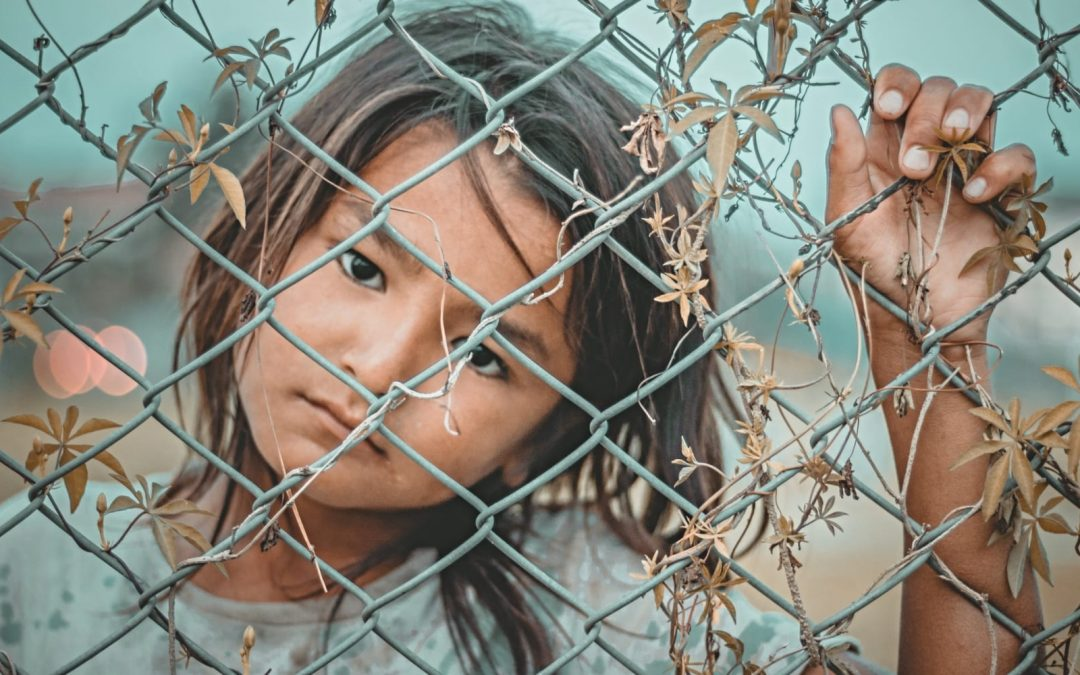 A young girl looking through a chain link fence