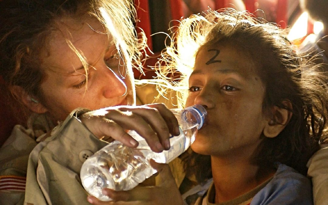 A female military solider giving water to a young girl
