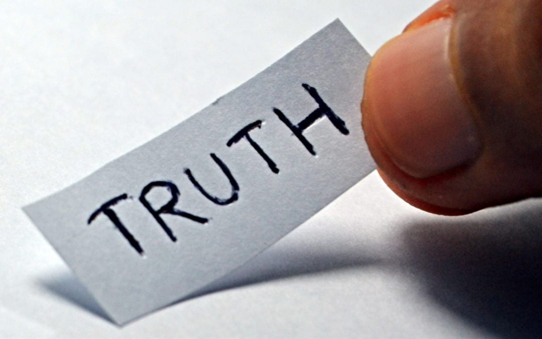 The word truth written in ink on a small piece of white paper