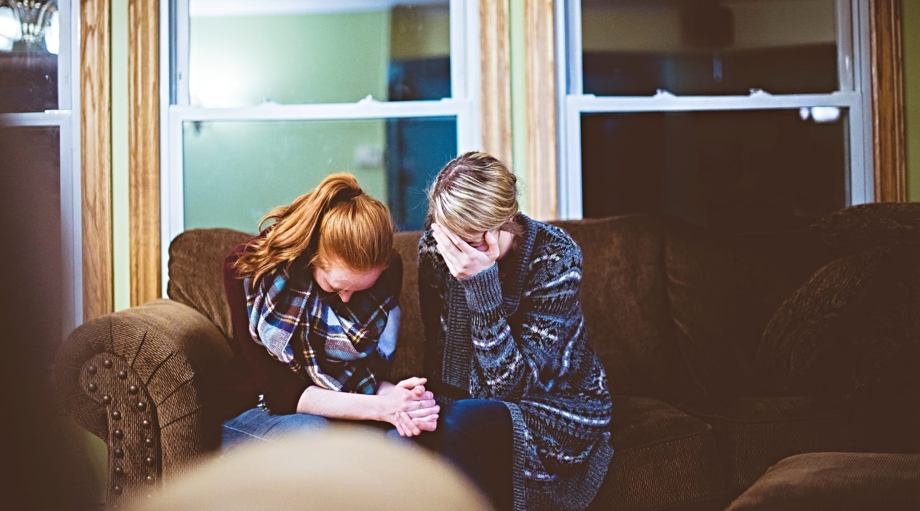 Two women sitting on a couch crying with their heads down