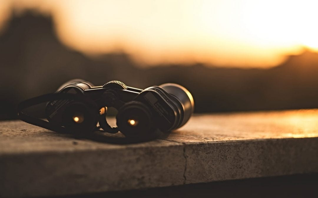 Binoculars sitting on a concrete wall as the sun sets