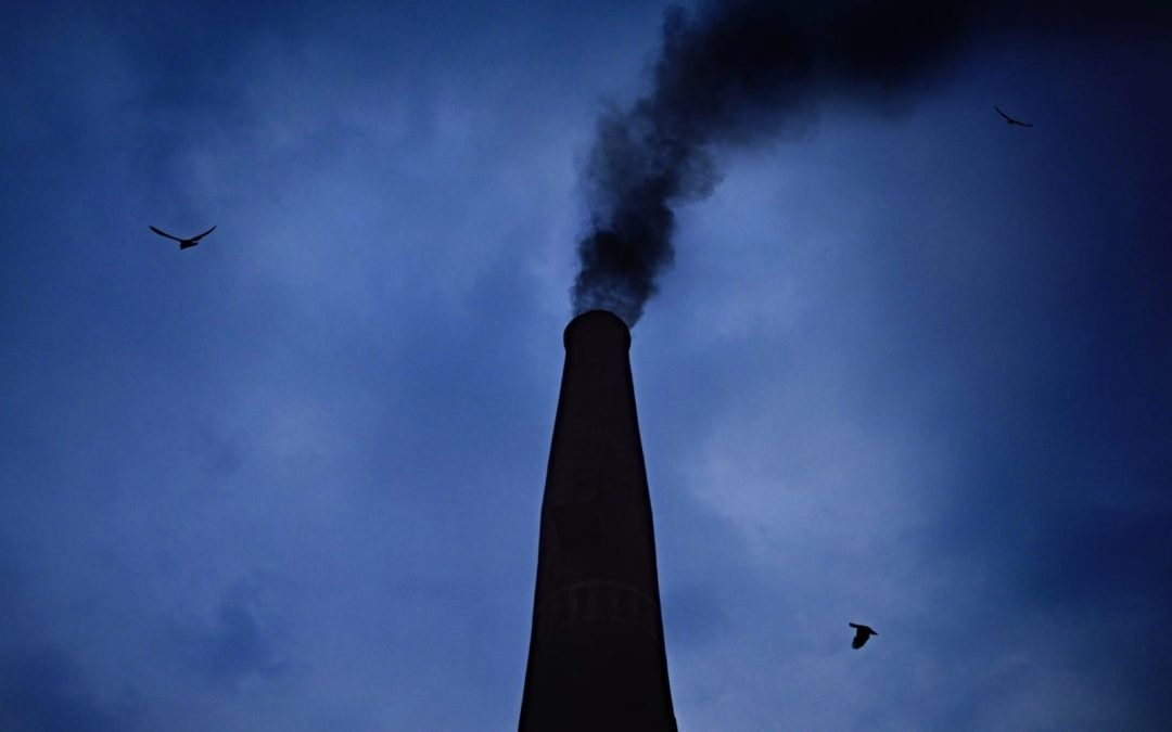 Black smoke rising into the air from a factory with a dark blue sky