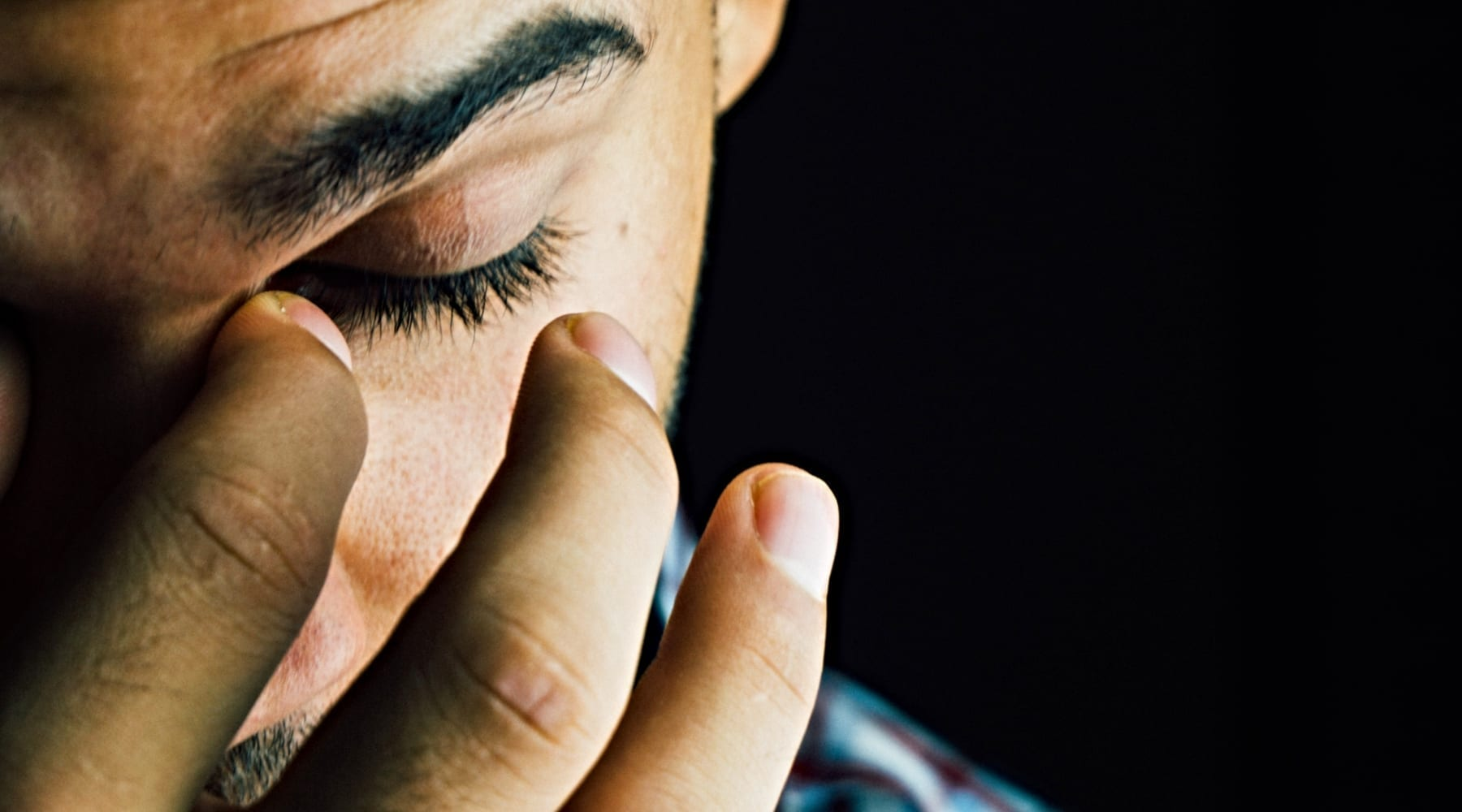 A man looking tired with hands on his face