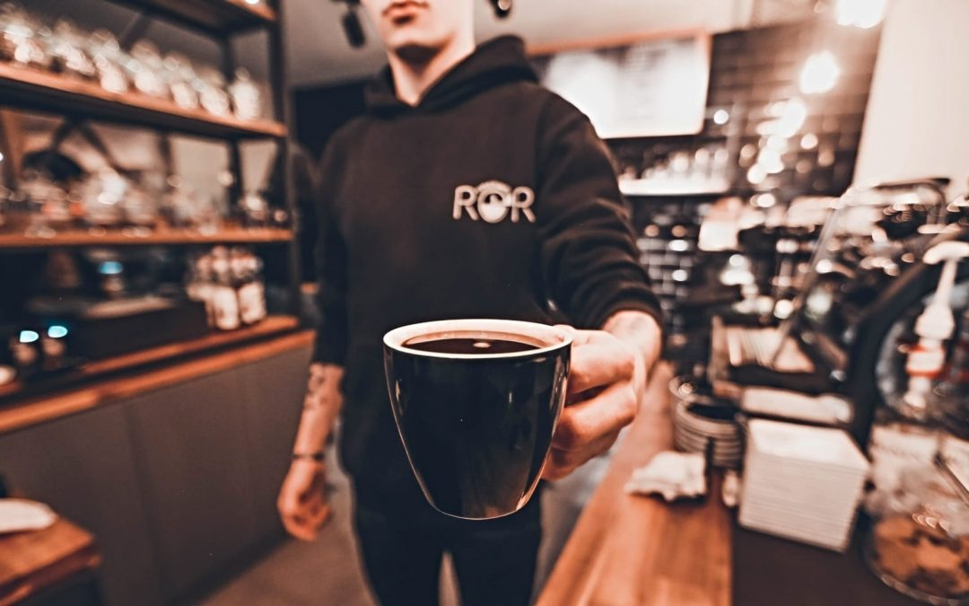 A barista holding out a cup of coffee
