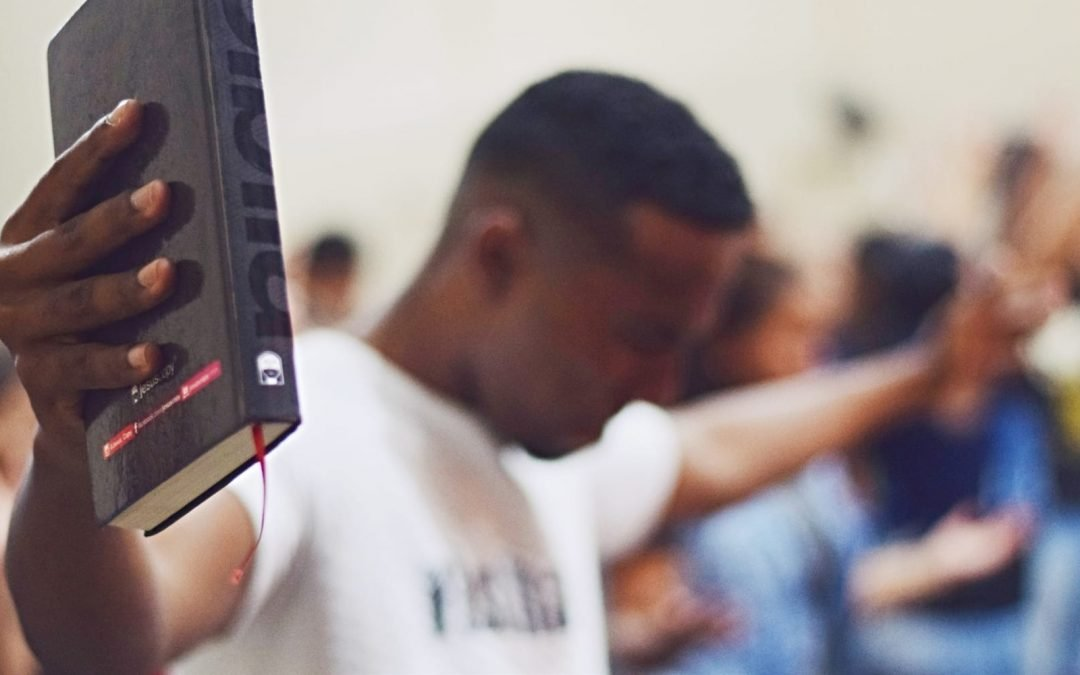 A Bible held up my a man during a worship service