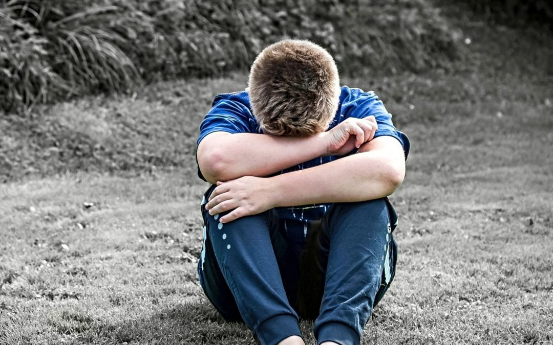 A young man sitting on the ground crying