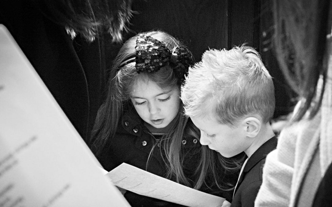 A young boy and girl looking at song lyrics on a piece of paper