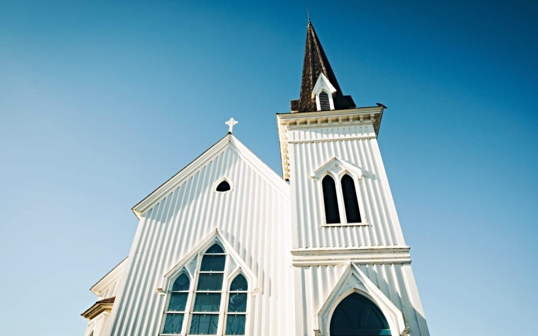 A white church photographed from below with a bright blue sky