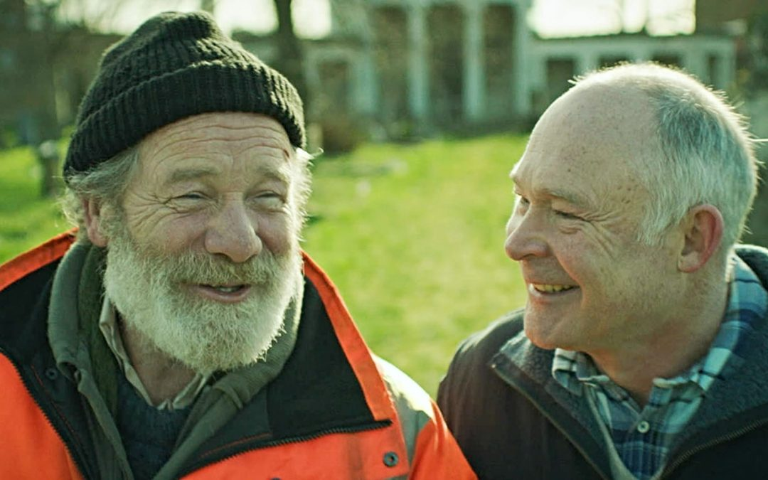 Two older men smiling while having a conversation