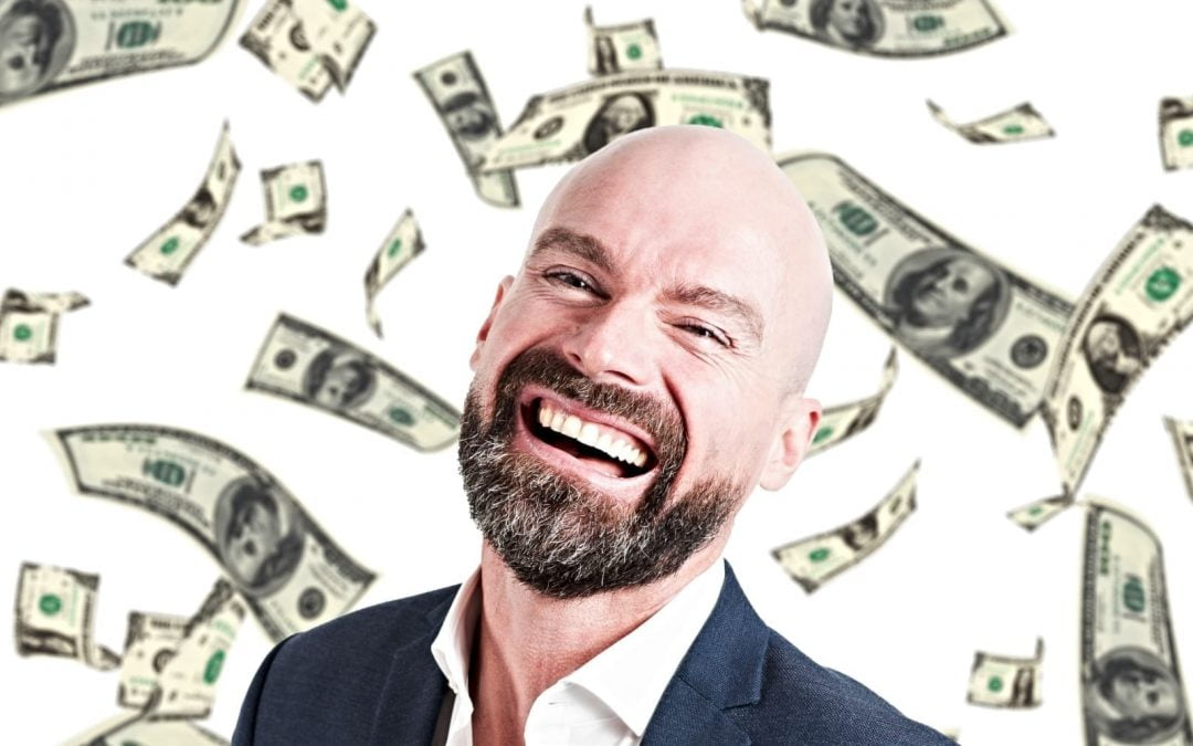 A man with a beard smiling with money falling in the air behind him